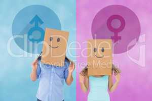 Composite image of couple wearing emoticon face boxes on their h