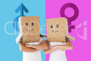 Composite image of couple wearing smiley face boxes on their hea