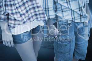 Composite image of couple in check shirts and denim holding hand