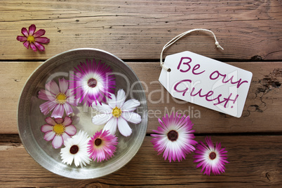 Silver Bowl With Cosmea Blossoms With Text Be Our Guest