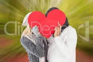 Composite image of couple in winter fashion posing with heart sh