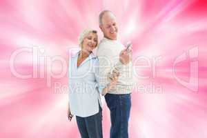 Composite image of happy mature couple looking at smartphone tog