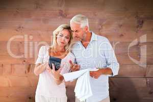Composite image of anxious couple working out their bills