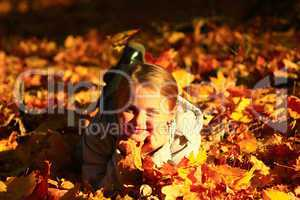 little girl laying in yellow leaves