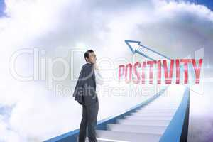 Positivity against red staircase arrow pointing up against sky