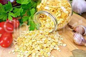 Pea flakes in jar with garlic on board