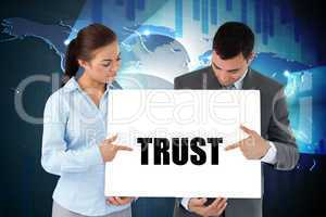 Business partners holding card saying trust