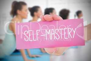 Woman holding pink card saying self mastery