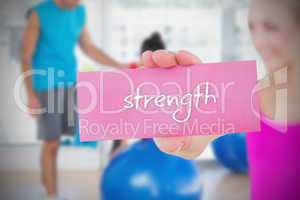 Fit blonde holding card saying strength