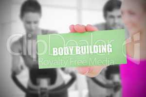 Fit blonde holding card saying body building