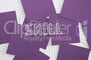 Skill against purple paper strewn over notepad