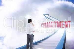 Commitment against red staircase arrow pointing up against sky