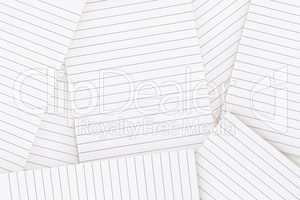 Lined paper strewn over surface