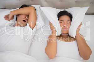 Annoyed woman covering her ears with pillows to block out snorin