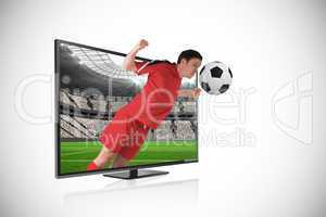 Football player in red heading ball through tv