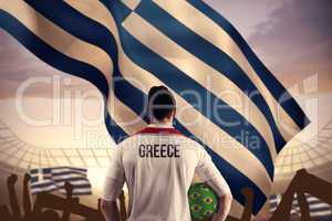Composite image of greece football player holding ball