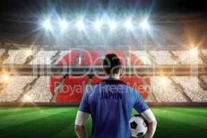Composite image of japan football player holding ball