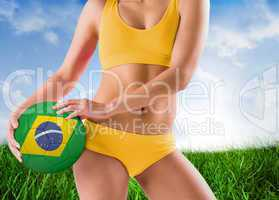 Composite image of fit girl in yellow bikini holding brazil foot
