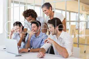 Business people laugh while looking at laptop