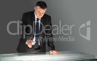 Concentrating businessman leaning on desk
