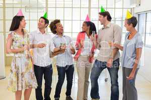 Coworkers laugh and celebrate accomplishment and enjoy party