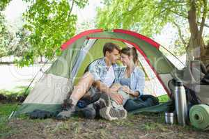 Cute couple sitting in their tent showing affection