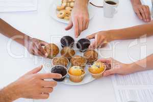 Hungry workers grabbing muffins