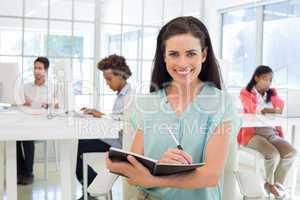 Attractive businesswomen writing in notebook with colleagues beh