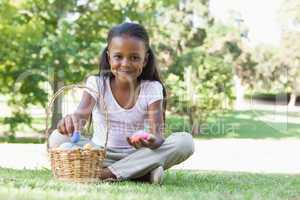 Little girl sitting on grass counting easter eggs smiling at cam