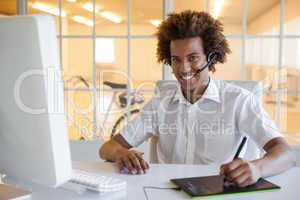 Casual young businessman using digitizer and headset at desk