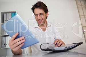 Casual smiling businessman organizing his schedule at his desk