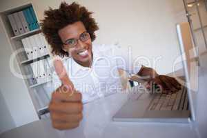 Casual businessman smiling at camera at his desk showing thumbs
