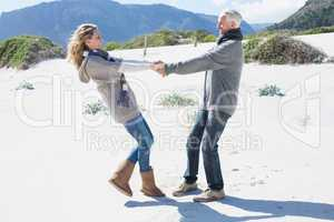 Smiling couple spinning on the beach in warm clothing
