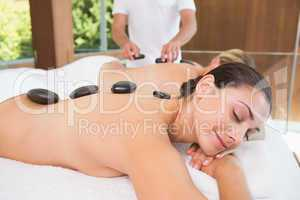 Happy friends lying on massage tables with hot stones on their b