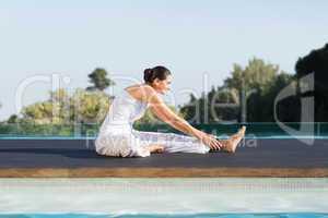 Peaceful brunette in janu sirsasana yoga pose poolside
