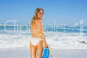 Fit smiling woman in white bikini holding snorkeling gear on the