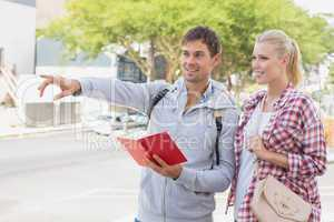 Young tourist couple consulting the guide book