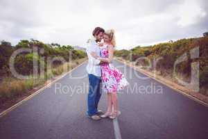 Cute couple standing on the road hugging