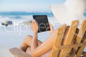 Woman in straw hat relaxing in deck chair on the beach using tab