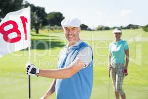 Happy golfer holding eighteenth hole flag with partner behind hi