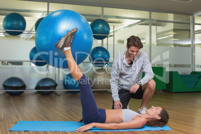 Trainer watching his client lift exercise ball with legs