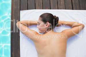 Tranquil brunette lying on towel poolside