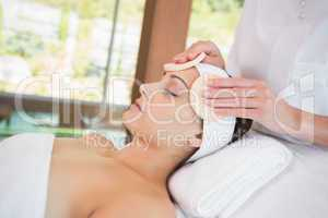 Peaceful brunette getting facial from beauty therapist