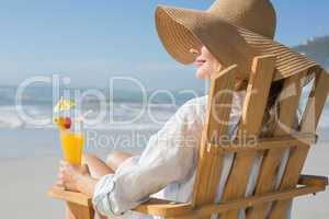 Smiling blonde relaxing in deck chair by the sea holding cocktai
