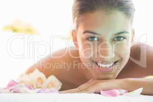 Smiling brunette lying on towel with rose petals