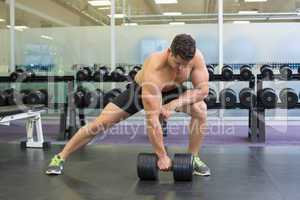 Shirtless bodybuilder lifting heavy black dumbbell in a lunge
