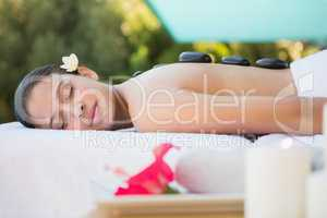 Smiling brunette lying on towel having a hot stone massage
