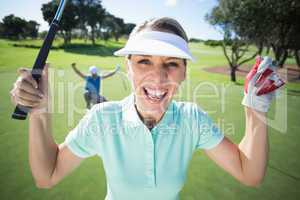Lady golfer cheering at camera with partner behind