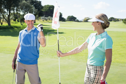 Lady golfer holding eighteenth hole flag for cheering partner