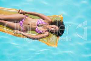 Happy woman lying on lilo in swimming pool
